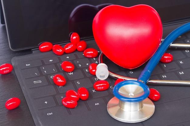 Blauwe stethoscoop met rode pillen op zwart modern laptop toetsenbord