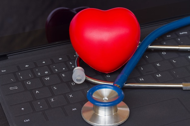 Blauwe stethoscoop op zwart modern laptop toetsenbord met rood hart
