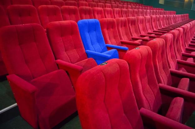 Blauwe stoel tussen rijen rode stoelen in het moderne theater. concept bioscoopscène