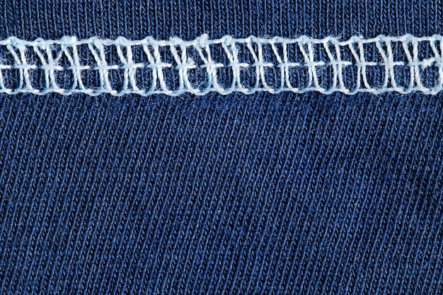 Blauwe stof en binnennaad met witte draden, achtergrondstructuur, close-up macroweergave