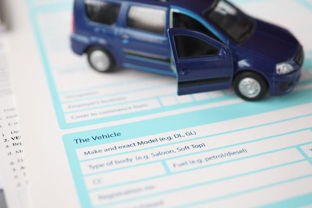 Blauwe stuk speelgoed auto die zich op verzekeringsdocument bevindt