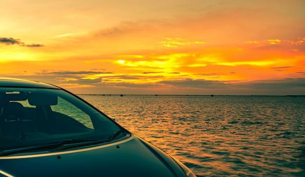 Blauwe suv-auto met sport en modern die ontwerp op betonweg door het overzees bij zonsondergang wordt geparkeerd.