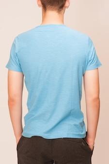 Blauwe t-shirt op een jonge man geïsoleerd, terug