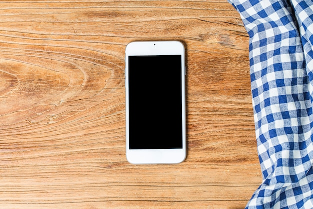 Blauwe tafelkleed op witte achtergrond, kopieer ruimte, bovenaanzicht. mobiele telefoon