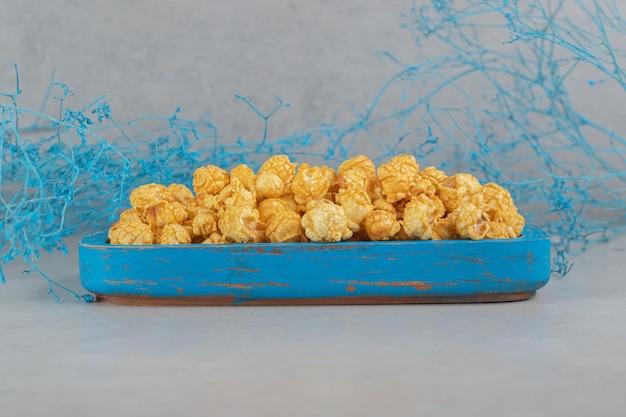 Blauwe takken naast een kleine schotel van karamelpopcorn op marmeren tafel.