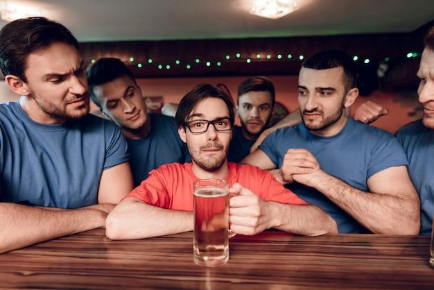 Blauwe teamsportfans bij bar die rood team omringen.