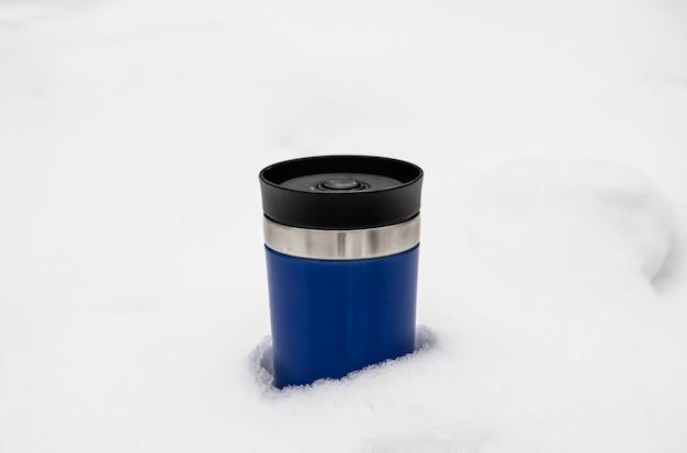 Blauwe thermocup met hete thee op witte sneeuw.