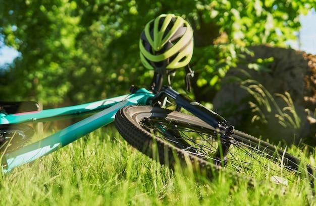 Blauwe tienerfiets en helm ligt op groen gras
