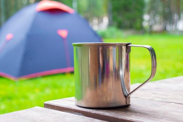 Blauwe toeristische tent bij achtergrond en metalen mok met thee of koffie op houten tafel. close-up van reizen
