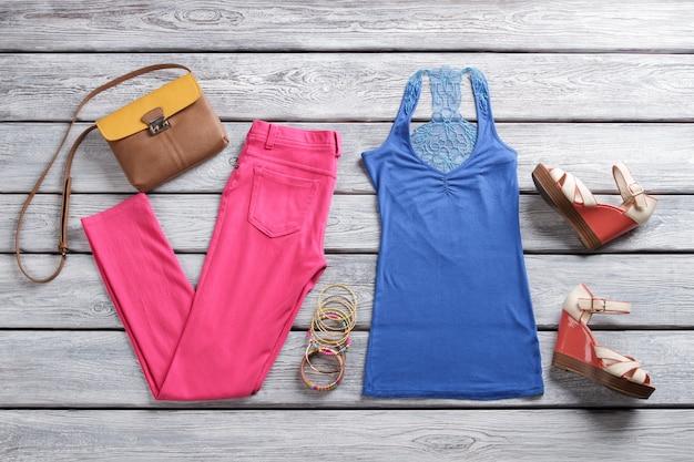 Blauwe top en roze broek. tweekleurige portemonnee en sandalen met sleehak. trendy zomerkleding voor dames. bijouterie en kleding op plank.