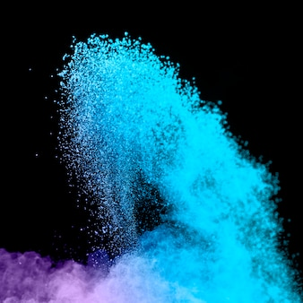 Blauwe uitbarsting van poeder op donkere achtergrond