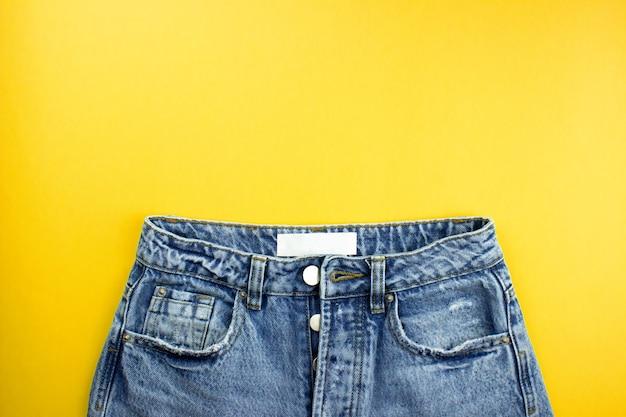 Blauwe unisex jeans met white label plat lag op gele achtergrond met kopie ruimte voor tekst, logo.