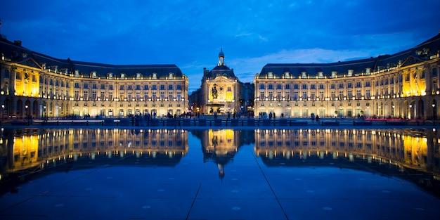 Blauwe uurgebouwen weerspiegeld in de waterspiegel tegenover place de la bourse in de franse stad bordeaux