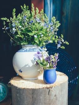 Blauwe veldbloemen in vaas op houten muur