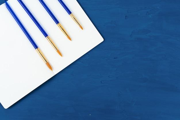 Blauwe verfborstels op klassieke blauwe achtergrond, mening van hierboven