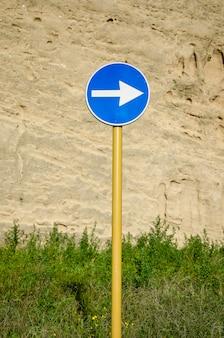 Blauwe verkeersbord met pijl op verweerde oude muur