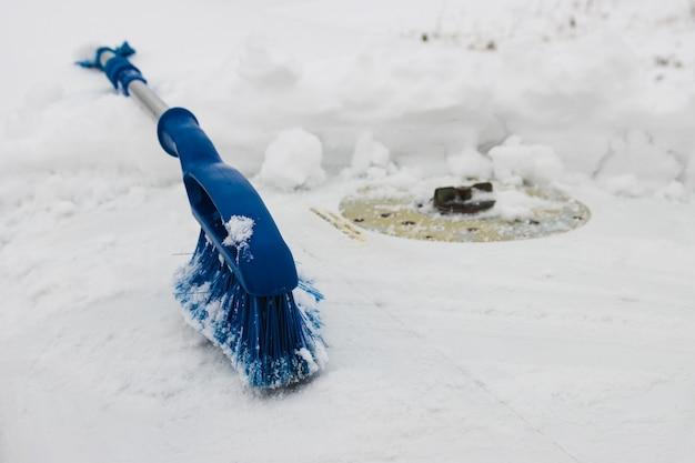 Blauwe verwijderborstel verwijdert sneeuw van de vliegtuigvleugel
