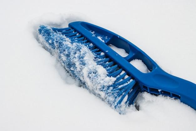 Blauwe verwijderingsborstel verwijdert sneeuw van de voorruit van de auto op een winterse dag, sneeuwval.