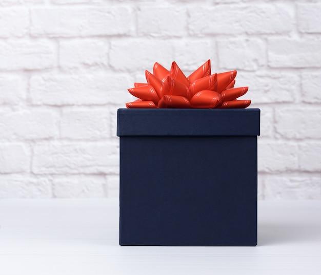 Blauwe vierkante kartonnen doos met rode strik