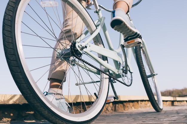 Blauwe vintage fiets met witte wielen op een zonnige zomeravond