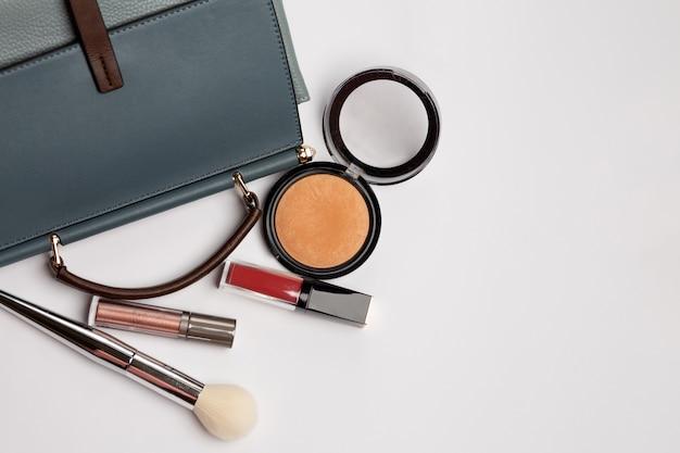Blauwe vintage portemonnee met bronzer, rode vloeibare lippenstift en penseel over een grijze achtergrond. lege ruimte
