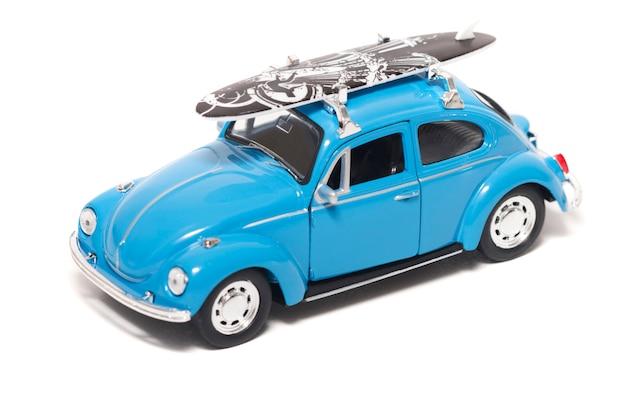 Blauwe vintage speelgoedauto met surfplank