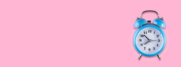 Blauwe vintage wekker op licht roze kleur achtergrond