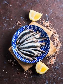 Blauwe vis. ansjovis in een schotel met roze zout