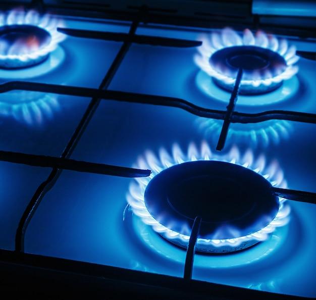 Blauwe vlammen van gas die van een keukengasfornuis branden