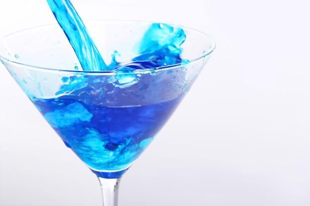 Blauwe vloeistof gieten in glas