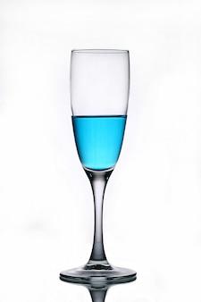 Blauwe vloeistof in een champagneglas op een witte achtergrond.