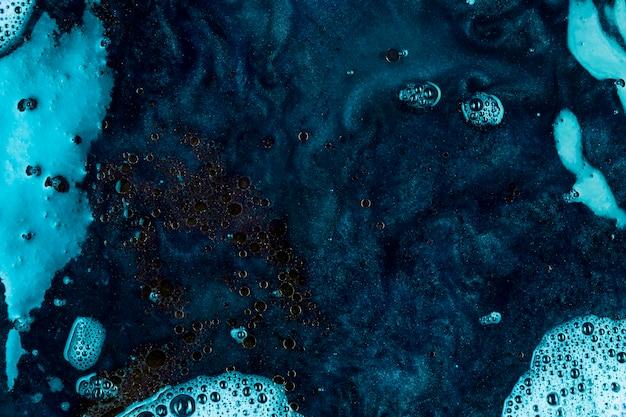 Blauwe vloeistof met zwarte klodders