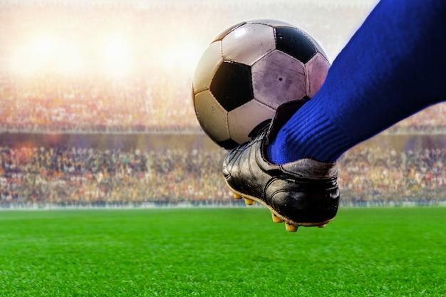 Blauwe voetballer die balactie in het stadion schoppen