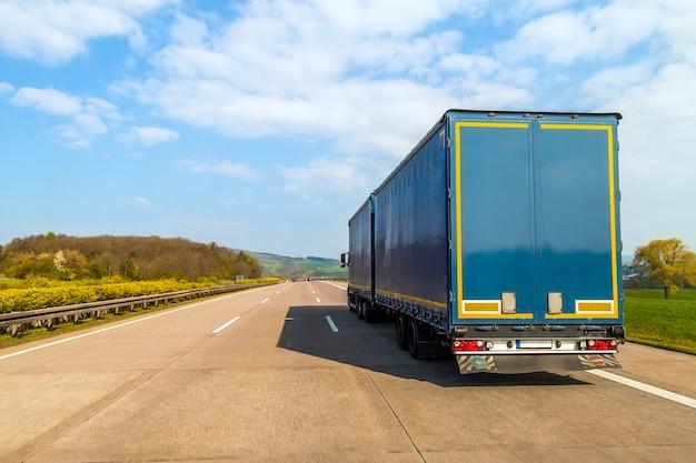 Blauwe vrachtvrachtwagen op een lege snelweg