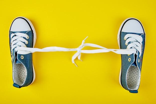 Blauwe vrouwelijke of mannelijke tennisschoenen op gele document achtergrond.
