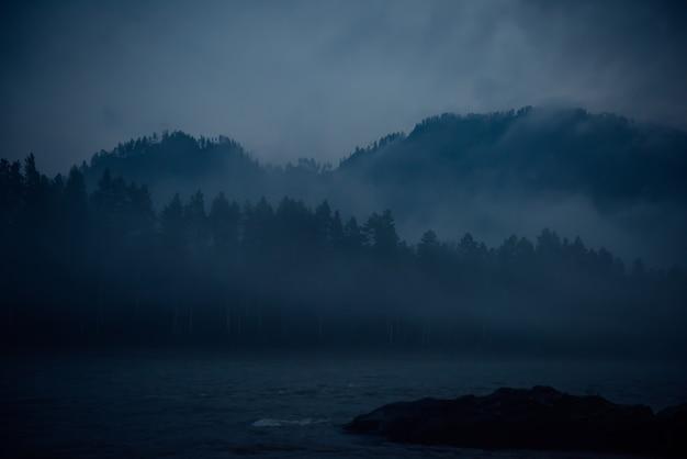 Blauwe waas, mystieke mistige ochtend. fantastisch landschap, dikke mist over een bergrivier in de schemering.