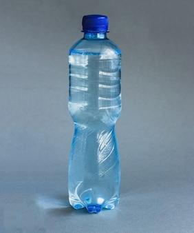 Blauwe waterflessen op grijs