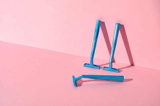 Blauwe wegwerpscheermessen op roze document achtergrond, exemplaarruimte