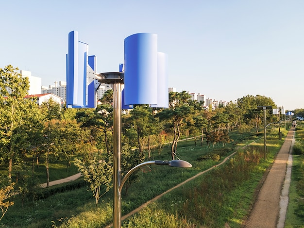 Blauwe windturbine en lantaarn in een zijaanzicht van het park.