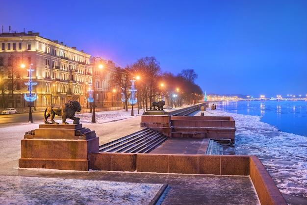 Blauwe winterochtend in st. petersburg met uitzicht op de rivier de neva en de leeuwen op de pier