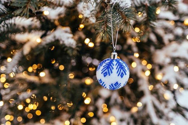 Blauwe witte kerstmisbal op dichte omhoog gouden gele lichte bokehachtergrond van de sparrentak