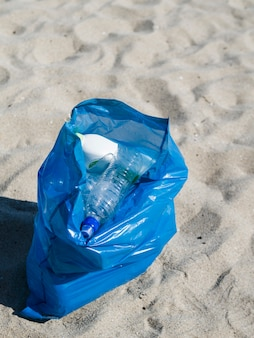 Blauwe zak plastic afval op zand bij strand