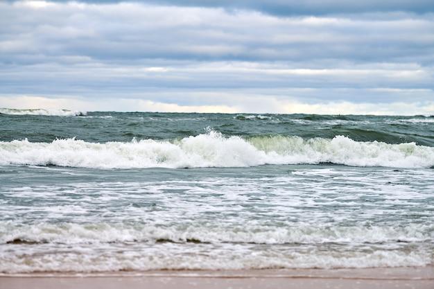 Blauwe zee en prachtige bewolkte hemel, zandstrand, landschap van de oostzee. borrelende en schuimende zeegolven.