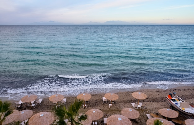 Blauwe zee en strand met parasols in fourka scala, halkidiki, griekenland Premium Foto
