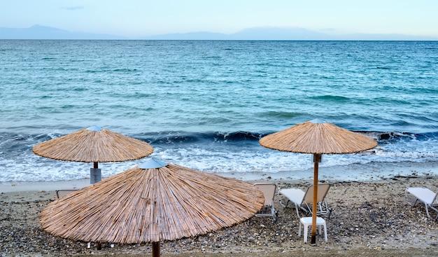 Blauwe zee en strand met parasols in fourka scala, halkidiki, griekenland
