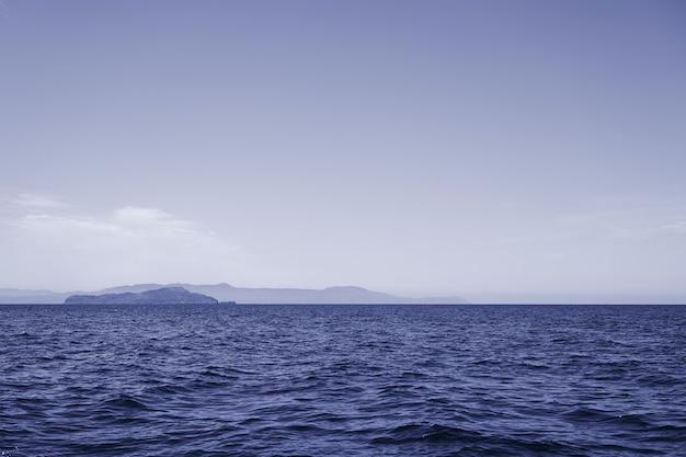 Blauwe zee met rotsachtige grassen als natuurlijke achtergrond. kopieer ruimte.