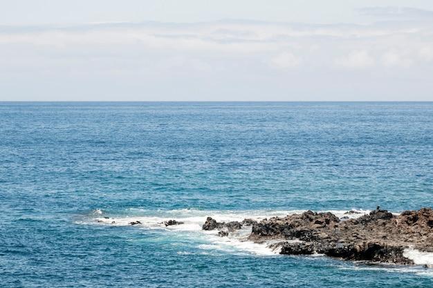 Blauwe zee met rotsachtige kust