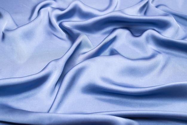Blauwe zijde of satijn luxe stof textuur. bovenaanzicht.