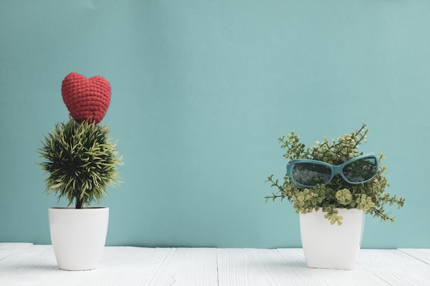 Blauwe zonnebril met kleine decoratie boom in witte vaas en rood hart