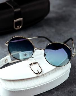 Blauwe zonnebril op de witte kast en grijze oppervlak